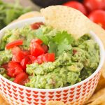 a bowl of Zesty Guacamole next to a pile of tortilla chips
