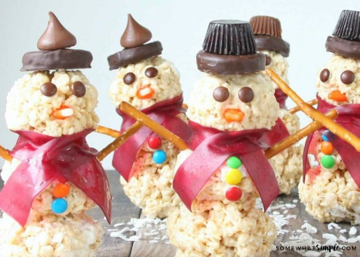 5 finished Snowman Rice Krispie Treats. some have peanut butter cup hats and others have hershey kisses for hats.