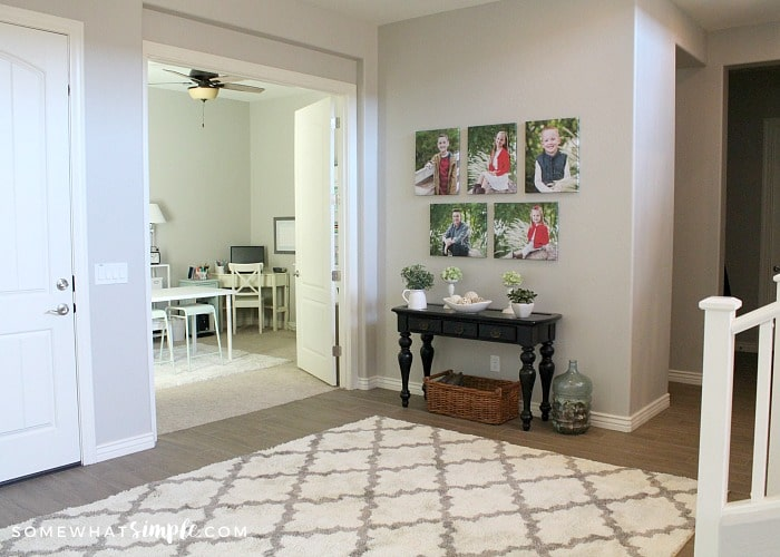 the entry way to a home with a white rug on the floor. There is a small black table with family pictures above it. From this angle you are looking through the entry way into a home office.