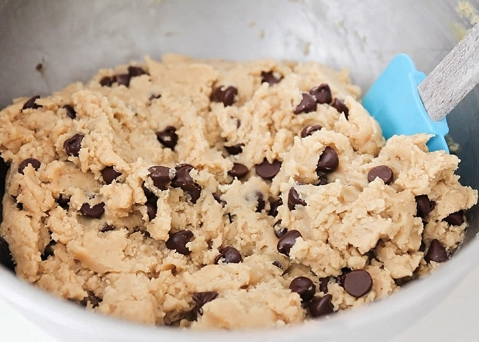 dough for the chocolate chip cookie base being stirred in a metal bowl with a blue spatula