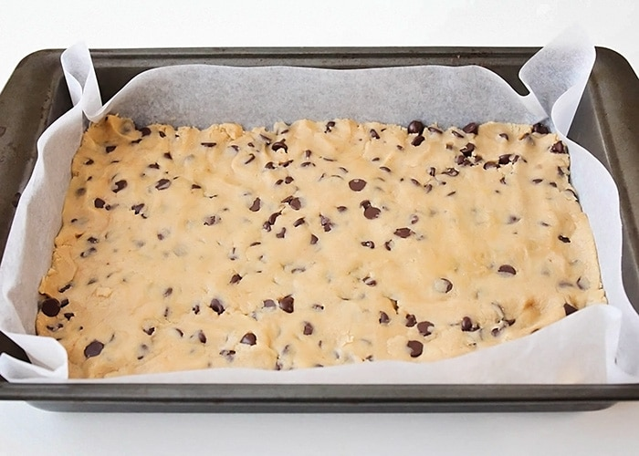 the cookie bar dough base spread out in a parchment paper lined baking pan
