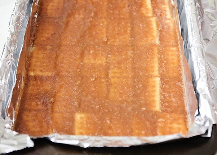 a baking sheet with club crackers topped with a butter mixture