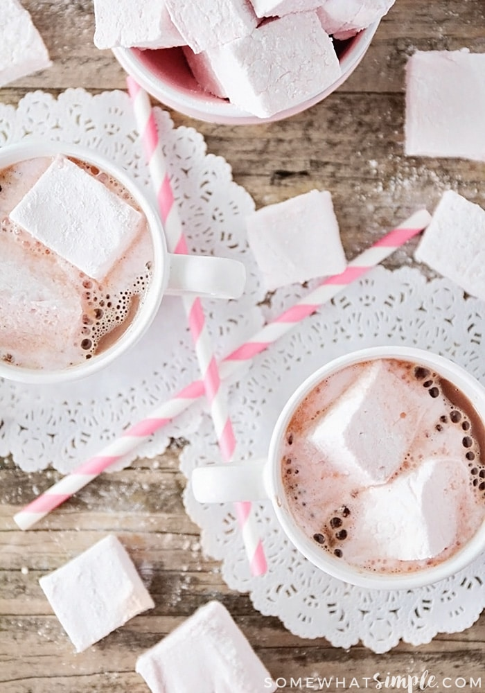 looking down on two mugs of hot chocolate and a pink bowl with Homemade Strawberry Marshmallows inside