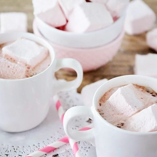 two cups of hot chocolate that have Homemade Strawberry Marshmallows floating in them. Behind the mugs is a bowl of more marshmallows.