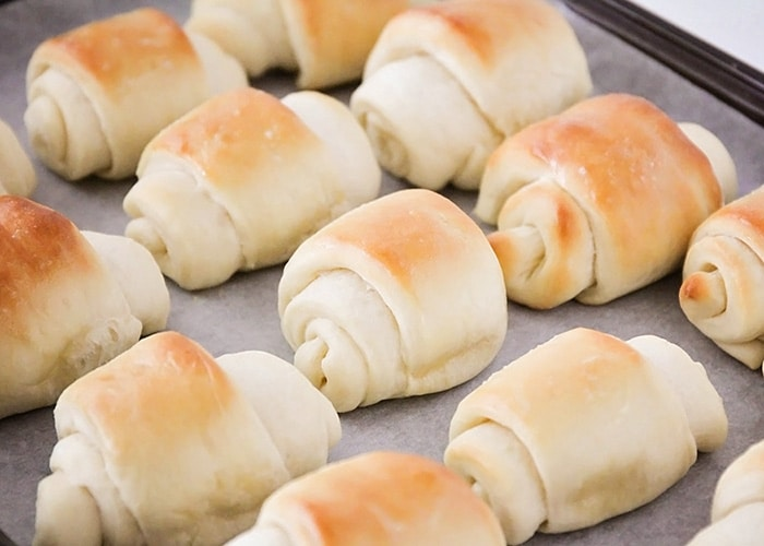 a tray of baked lion house rolls