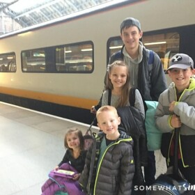 five children standing on the Eurostar train platform in London. Behind them is a high speed train that is headed to Paris.
