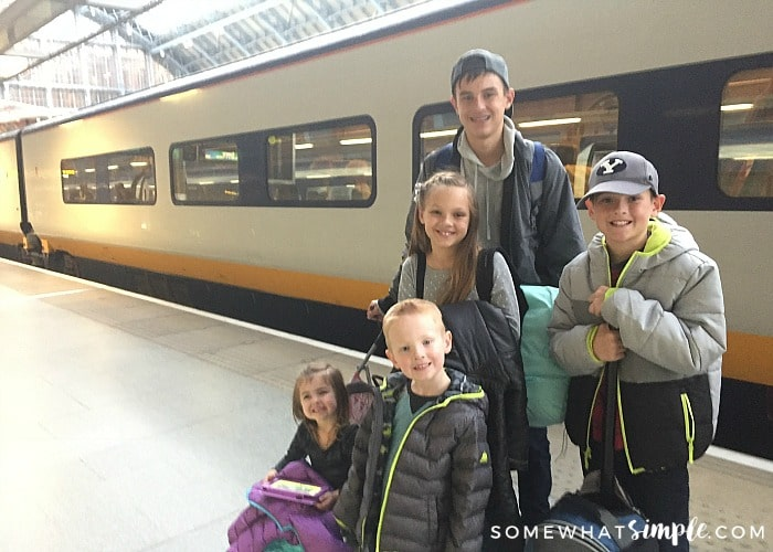 five children standing on the Eurostar train platform in London, waiting to board their train. Behind them is a high speed train that is headed to Paris.