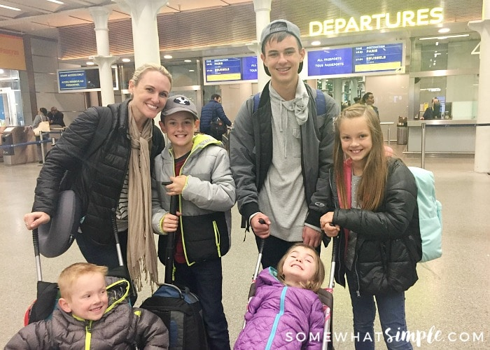an attractive woman with her 5 kids standing outside of the departure gate at a train station in London