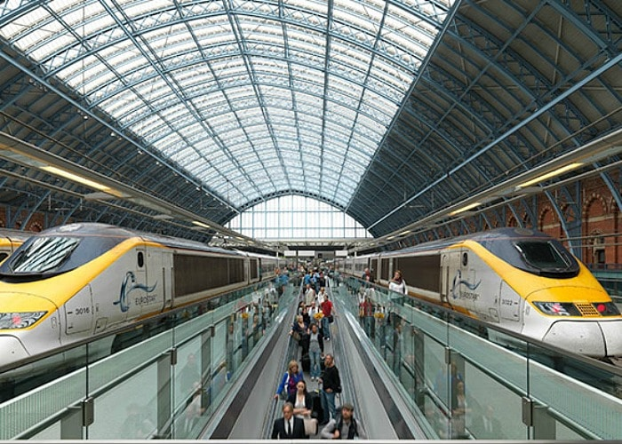 Inside St. Pancras station in London with a Eurostar bullet train on each side of the platform with a trail of people riding the moving walkway in between the trains. These trains are the best way to travel throughout Europe.