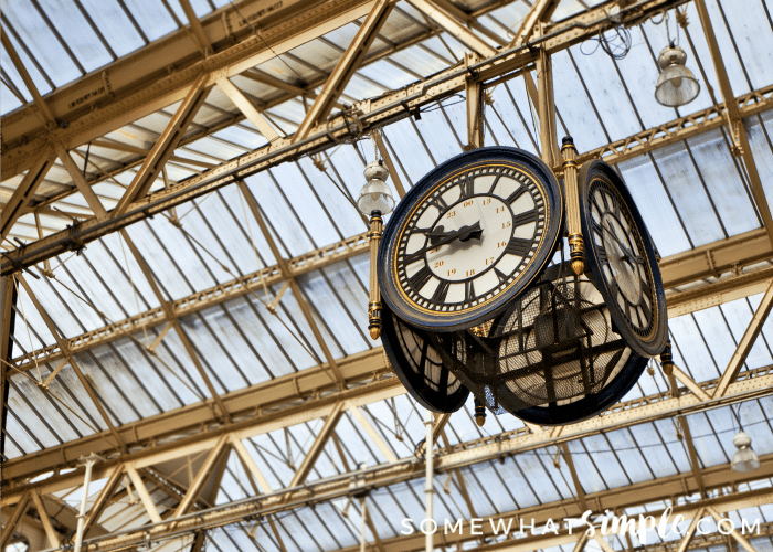 a clock hanging from St Pancras Station in London, England