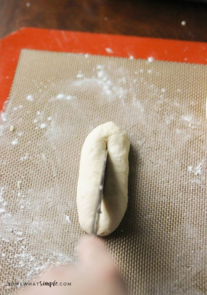 a piece of dough being sliced down the middle with a knife in order to be able to mold the bread into a heart shape