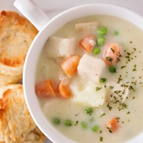 looking down on a bowl of chicken pot pie soup and biscuits