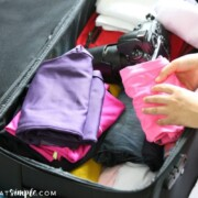 a suitcase filled with clothes, a camera and other essential items