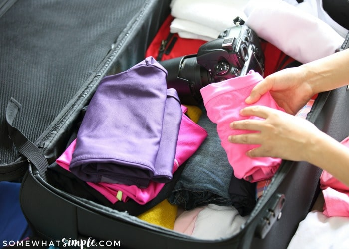 a suitcase filled with things you need to pack like clothes, a camera and other essential items