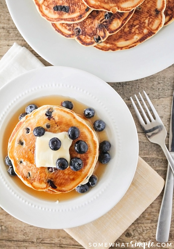 looking down on a pancake topped with butter, syrup and blueberries