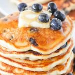 a stack of lemon blueberry pancakes topped with a pad of butter, syrup and fresh blueberries