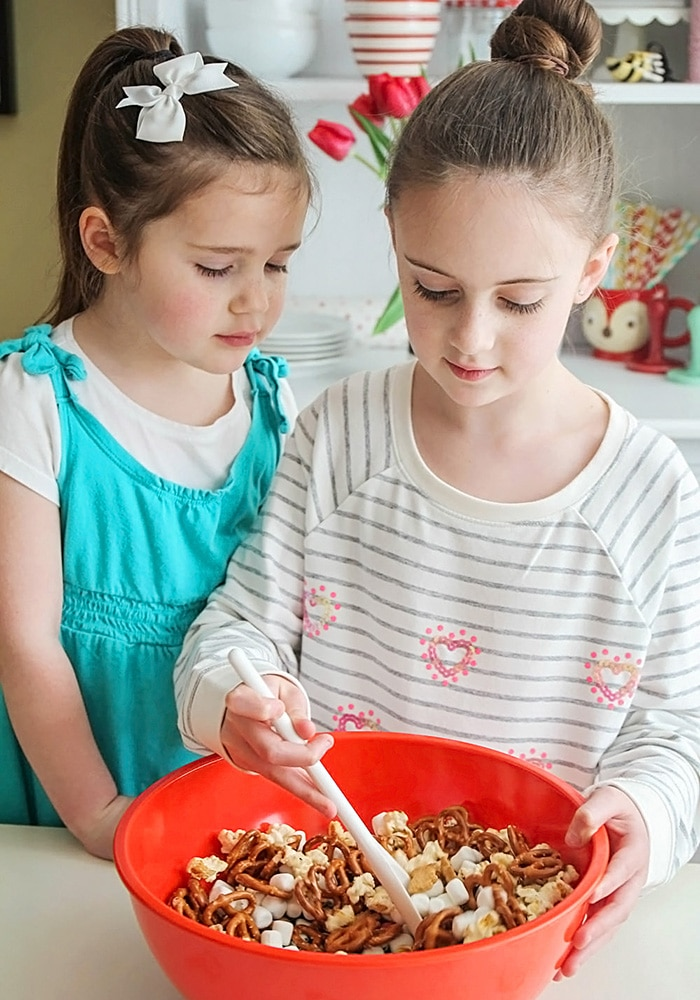 2 girls making a snack mix in a bowl