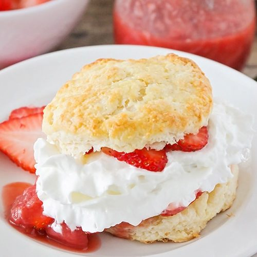 a piece of strawberry shortcake made with a biscuit and filled with sliced strawberries and whipped cream on a white plate. Additional strawberry slices are on the plate.