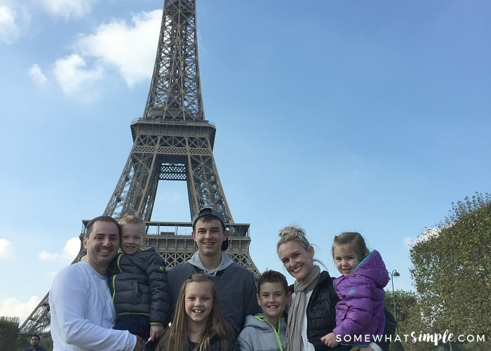 A family of seven standing in front of the Eiffel town on their European Vacation