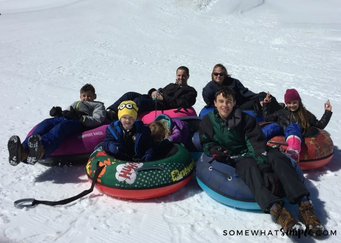 a family playing in the snow with innertubes