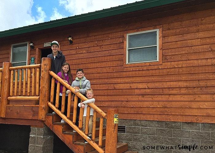 4 cute children next to a mountain cabin