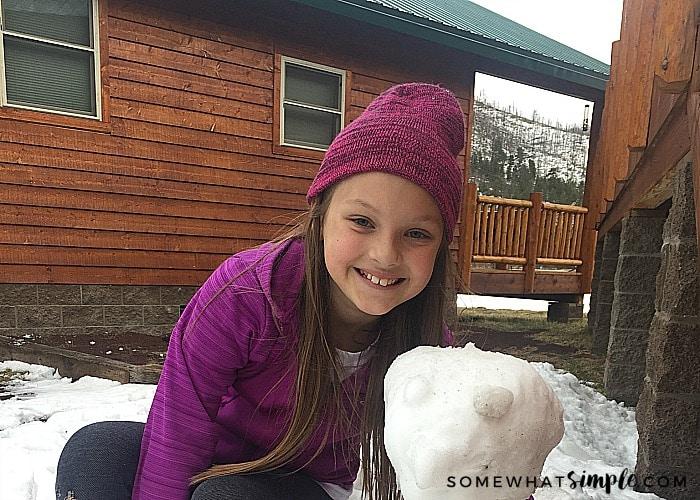 a cute girl next to a small snowman