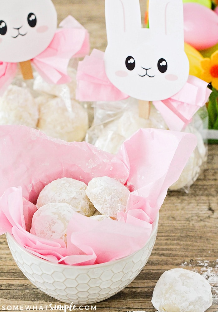 A white bowl filled with pink tissue paper and bunny tail cookies. Behind the bowl are two Easter bunny gifts filled with these easy cookies