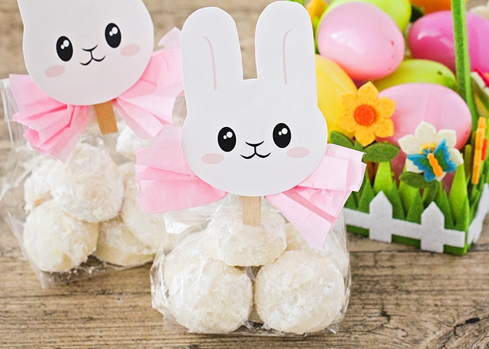 two packages of Easter bunny tail cookies wrapped in plastic with a pink bow and topped with an Easter bunny printable. Next to the cookie gift bags is an Easter basket filled with plastic eggs.