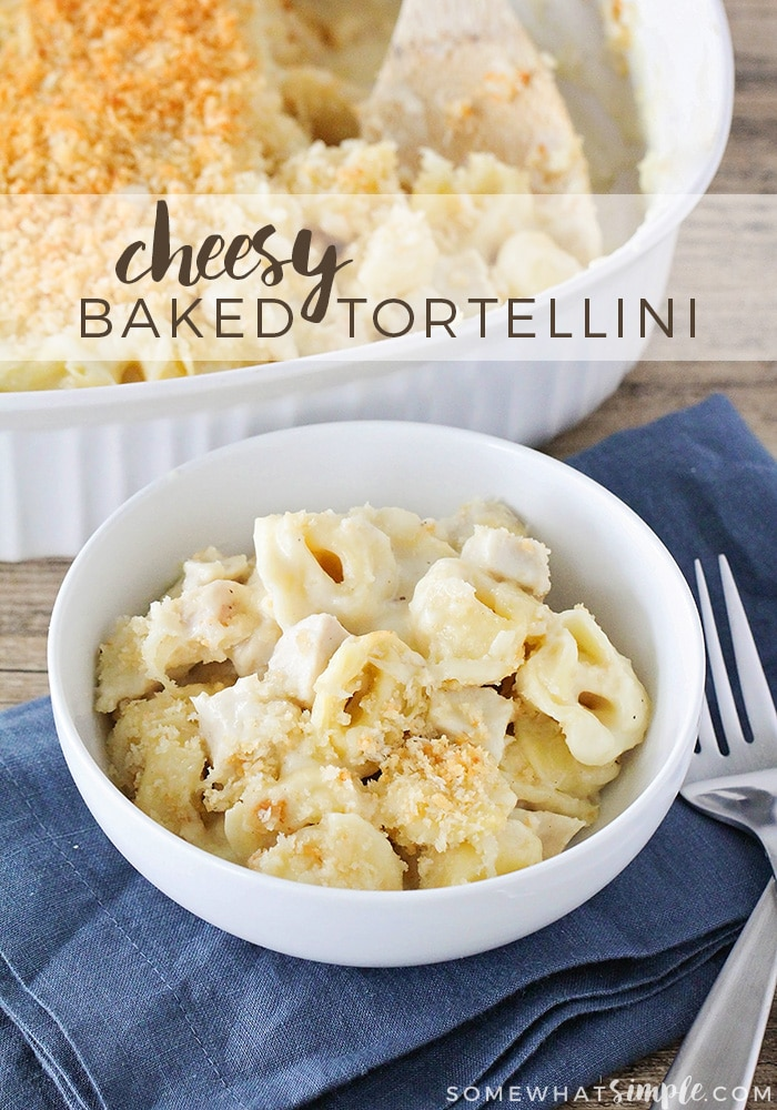 a white bowl filled with this tortellini bake recipe and it is topped with bread crumbs. The bowl is sitting on a blue cloth napkin and a fork is next to it. Behind the bowl is a casserole filled with this tortellini recipe. At the top of the image the words cheesy baked tortellini is written in a white translucent box.