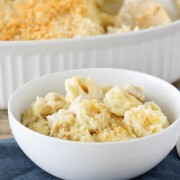 a white bowl filled with cheesy baked tortellini topped with bread crumbs. The bowl is sitting on a blue cloth napkin and a fork is next to it. Behind the bowl is a casserole filled with this tortellini recipe.