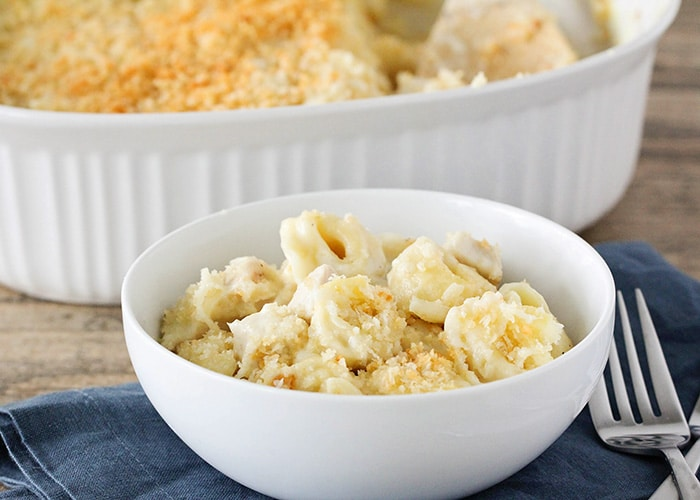 a white bowl filled with cheese baked tortellini topped with bread crumbs. The bowl is sitting on a blue cloth napkin and a fork is next to it. Behind the bowl is a casserole filled with this tortellini recipe.