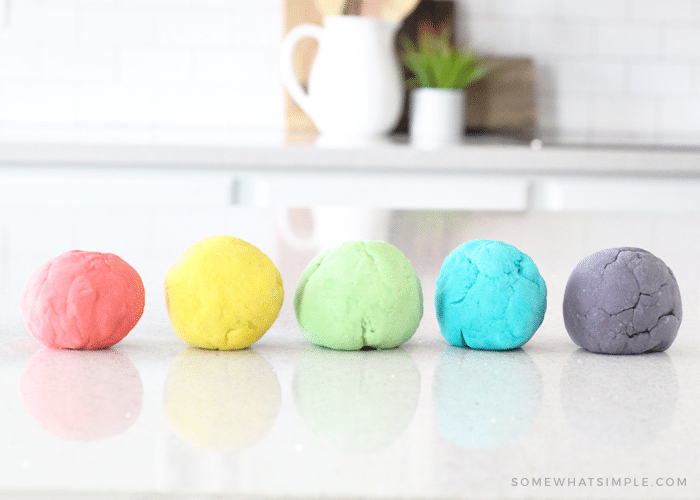 five different colored balls of homemade playdough sitting on a counter that were made with this easy recipe