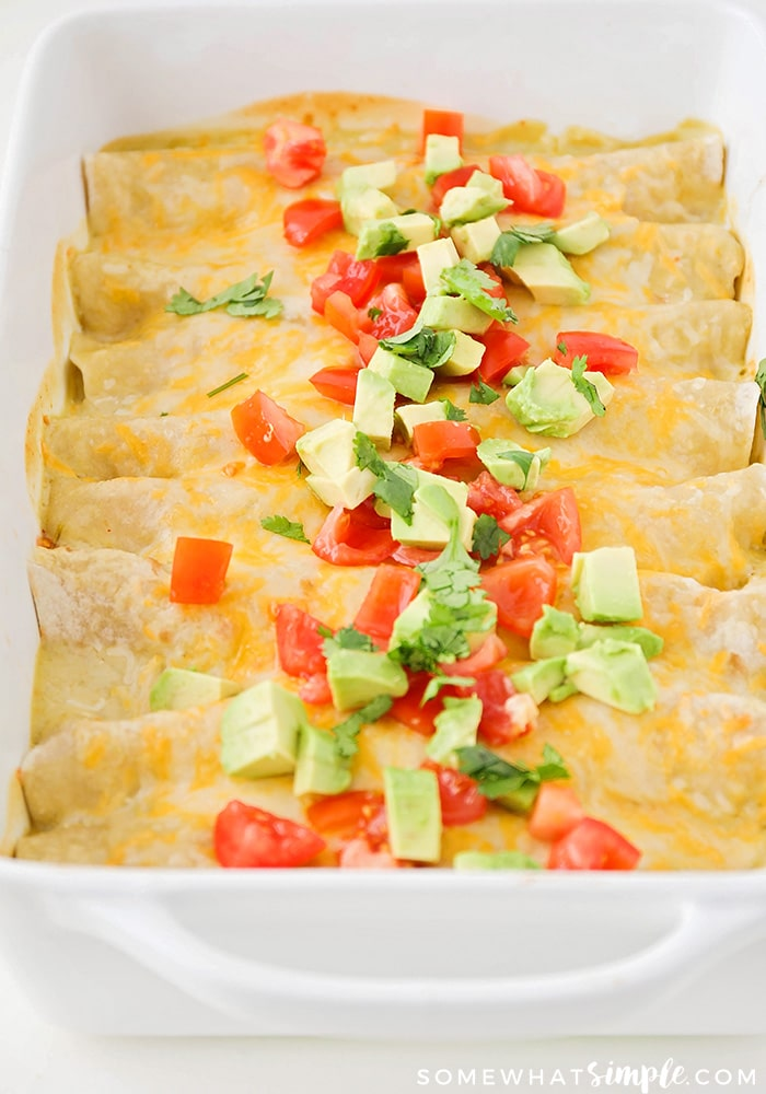 a tray of enchiladas topped with cheese, diced tomatoes and avocado