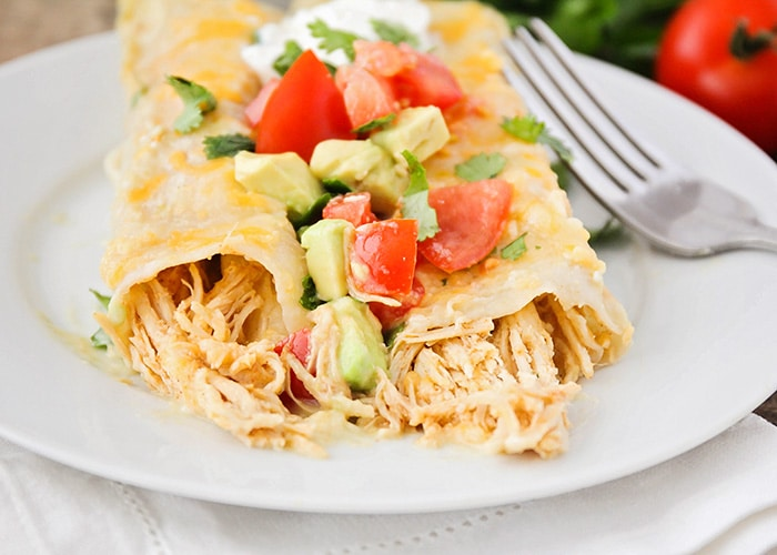 honey lime chicken enchiladas topped with tomatoes and avocado