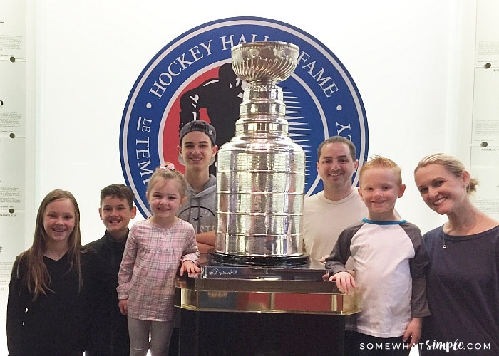a family of seven standing around the Stanley Cup at the Hockey Hall of Fame in Toronto Canada
