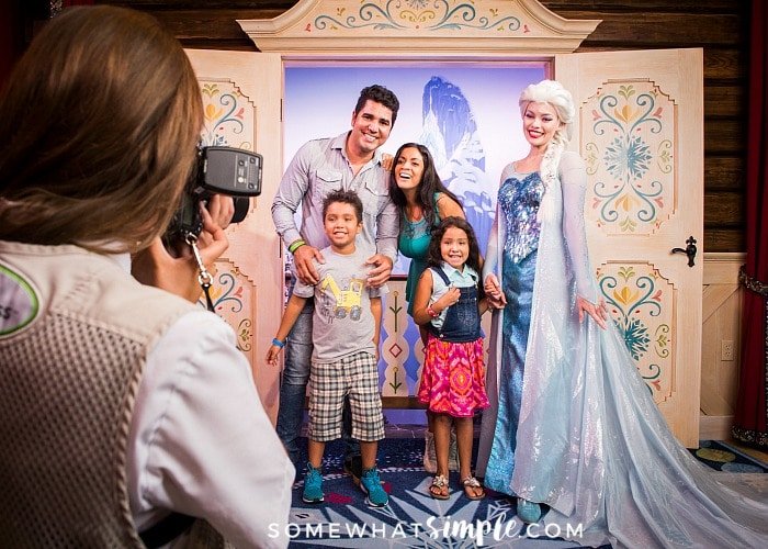 a family getting their picture taken with Elsa from the movie Frozen at the Magic Kingdom