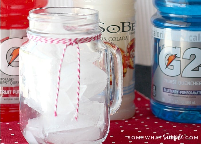 a glass Mason jar mug filled with ice. Next to the jar is a bottle of red Gatorade, a white Sobe pina colada drink and a bottle of blue sugar free Gatorade