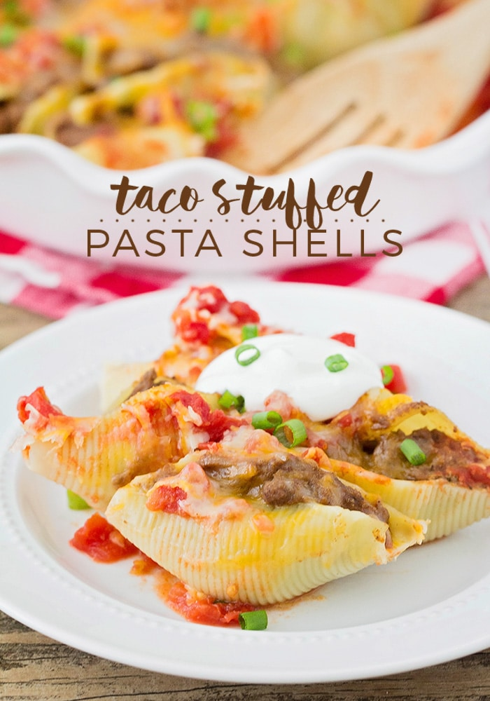 a white plate of Taco Stuffed Pasta Shells topped with sour cream and green onions