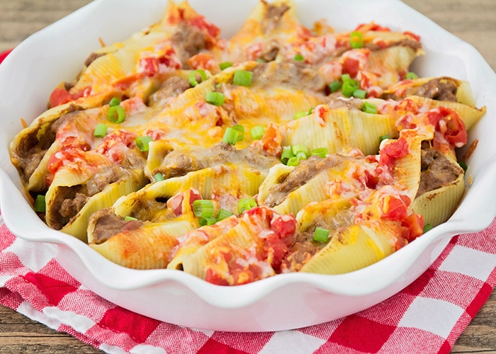 a casserole dish full of taco stuffed pasta shells covered with cheese, green onions and salsa
