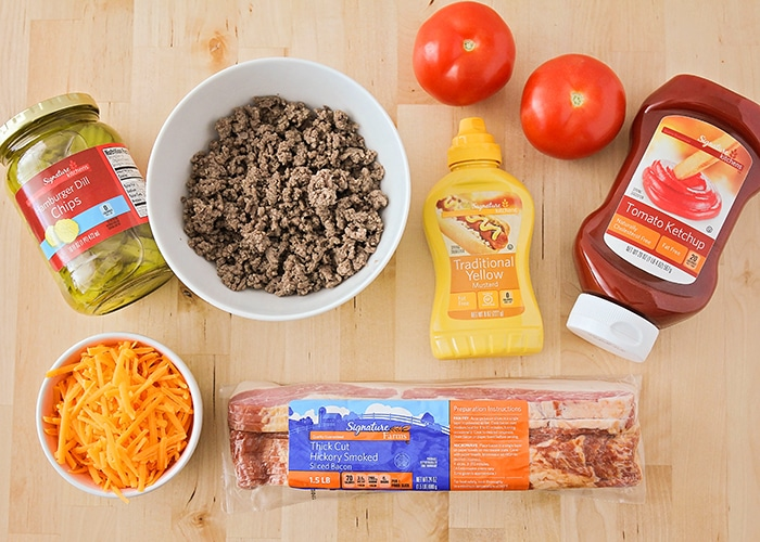 looking down on the ingredients needed to make this bacon cheeseburger pizza recipe; ground beef, pickles, cheese, bacon mustard, ketchup and tomatoes