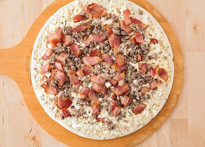 looking down on a raw pizza crust with cheese ground beef and bacon on top