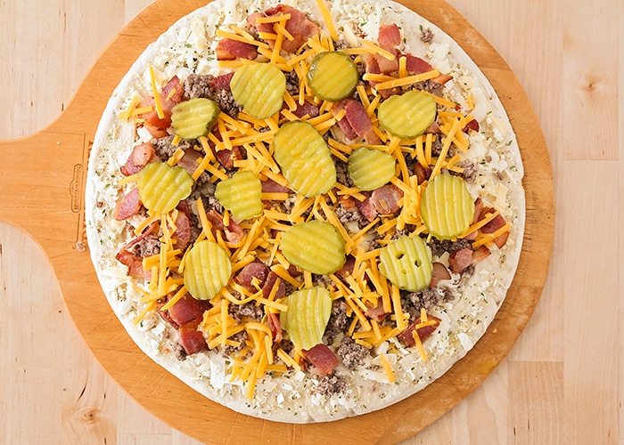 looking down on a raw pizza crust with cheese ground beef, bacon cheese and pickles on top before it is placed in the oven