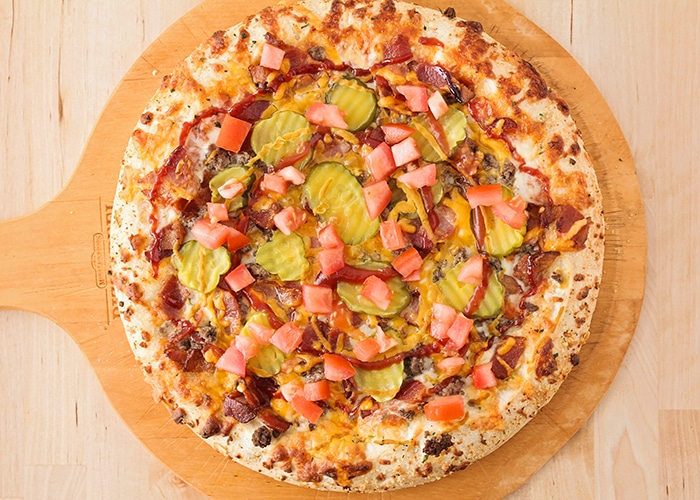 looking down on a baked bacon cheeseburger pizza with cheese ground beef, bacon cheese and pickles with a swirl of ketchup and mustard on top before it is placed in the oven