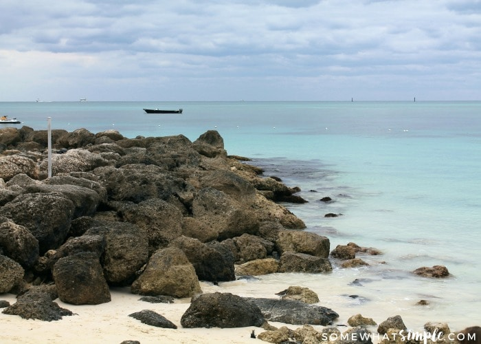 a view of a white sand beach in Freeport, Bahamas that has large rocks at the end of the beach. There are few small boats in the water off in the distance.