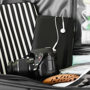 packing tips a camera, a tablet and a laptop case sitting on top of an open suitcase