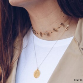 how to wear a necklace. pretty woman wearing a gold chain around her neck with a smaller necklace layered on top