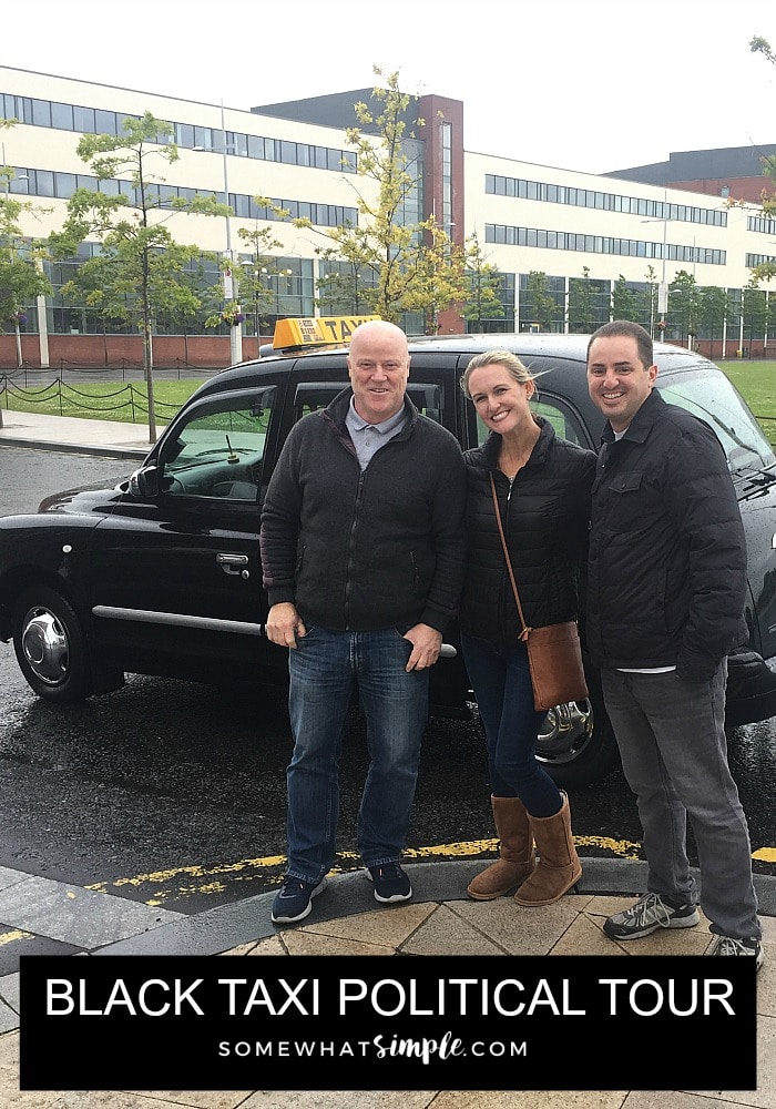 a hot blonde standing in between her husband and a taxi driver in Belfast Northern Ireland with a black cab behind them