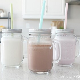 Chocolate, strawberry and vanilla Slim Fast shakes in mason jar glasses on a counter and each have a pastel colored straw