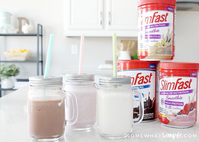 Chocolate, strawberry and vanilla Slim Fast shakes in mason jar glasses on a counter next to containers of Slim Fast smoothie mix