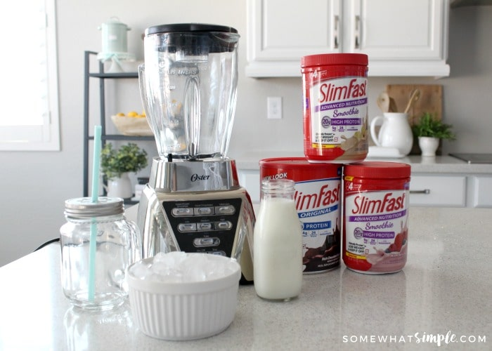 a blender sitting on a counter next to a mason jar glass, a jar of milk, a bowl of ice and cans of chocolate, strawberry and vanilla slim fast shake powders.